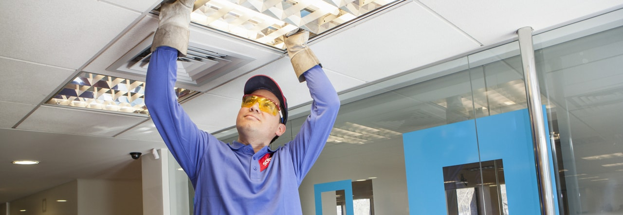 facilities management worker changing a light