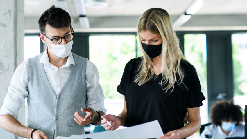Man and woman in masks reviewing documents