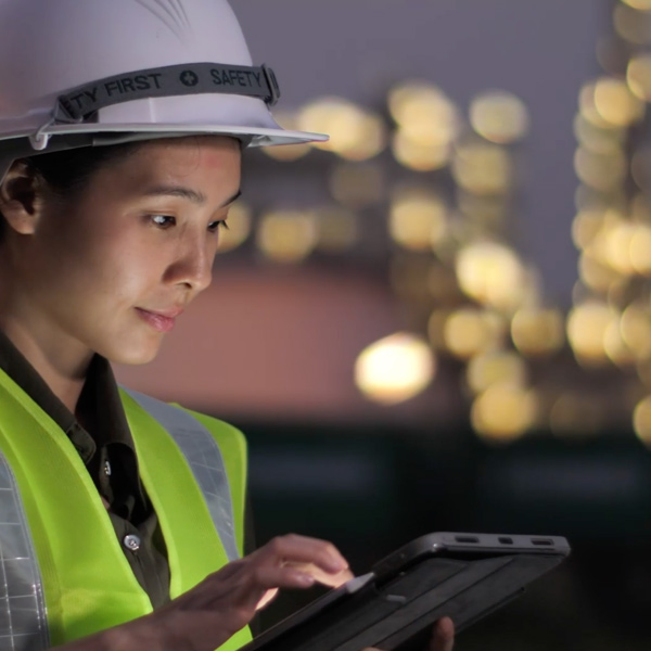 Woman in a hardhat working on tablet
